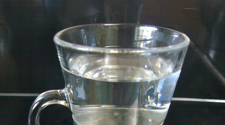 A half full glass of water with a handle on the black table. Face Yoga Method hot water benefits.