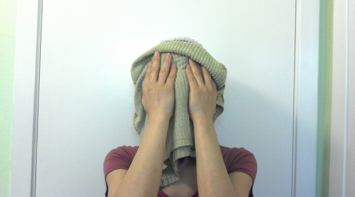 A woman holding green towel over her face.
