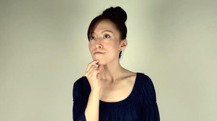 Fumiko Takatsu holding her chin while showing an exercise for firming cheeks.