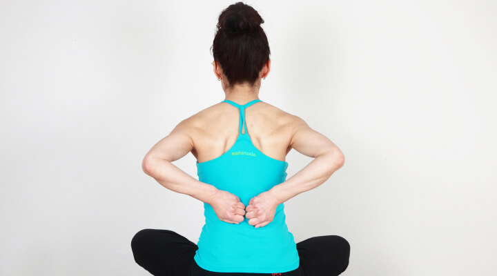 A woman sitting with legs crossed, her back facing camera while she is holding her fists on her lower back.