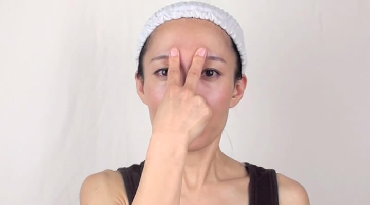 A woman with a white shower cap looking straight at the camera and holding two middle fingers on her eyebrows.