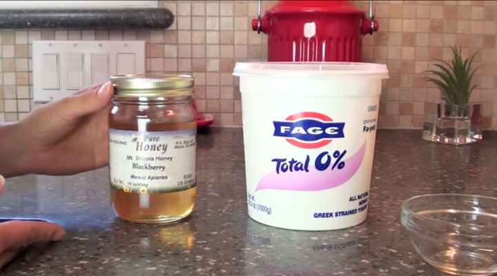 A white pint of greek yogurt next to a glass jar with honey on a brown kitchen countertop.