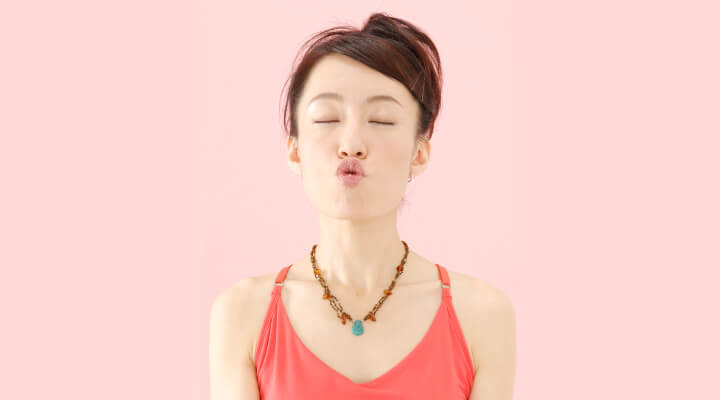 A woman with dark hair and in red sleeveless shirt holding her lips in O shape whit eyes closed.