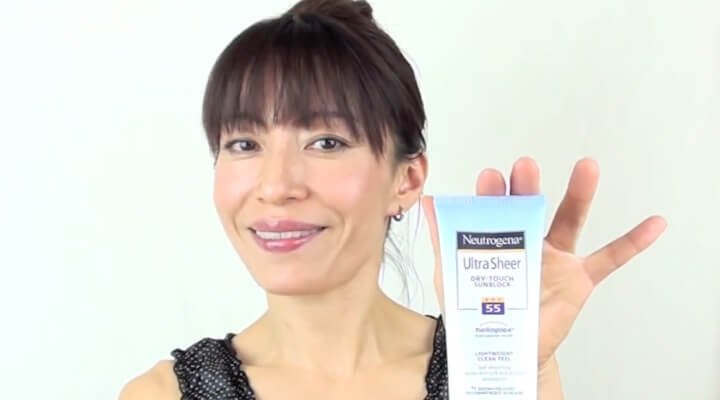 A woman with dark hair and bangs smiling and holding a sunscreen tube.