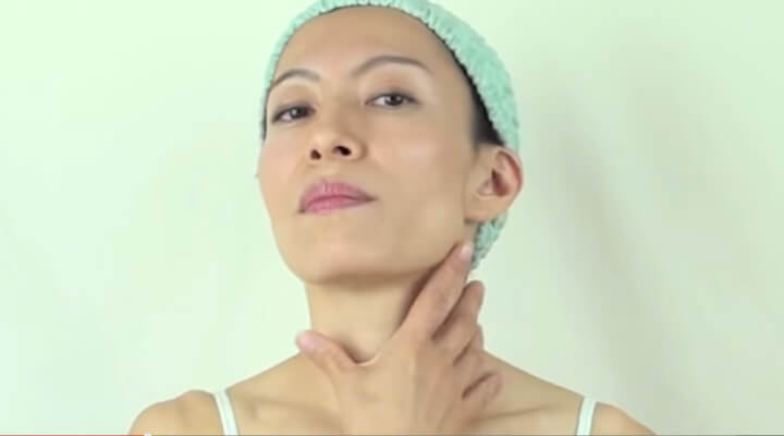 A woman with a green shower cap looking at the camera and holding her neck with one hand.