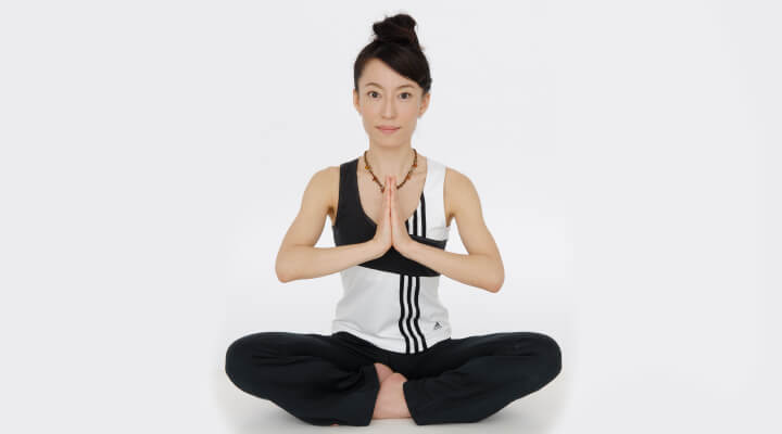 A woman in black and white sport gear, sitting in yoga pose with legs crossed and her hands next to her face in praying position.