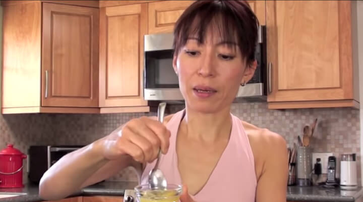 A woman i rose pink sleeveless shirt mixing a yellow mixture in a glass bowl with a spoon.