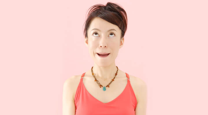 A woman in red sleeveless shirt looking up and and making expression with her mouth