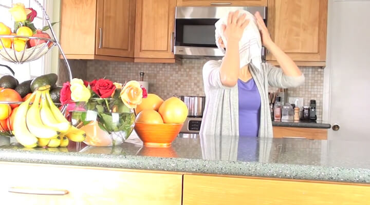 A person in the kitchen holding a white towel over her face.