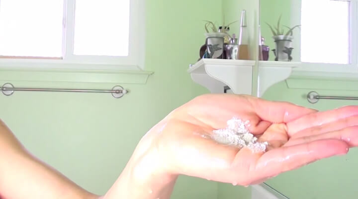 A hand holding a pile of white powder. Green bathroom in the background.