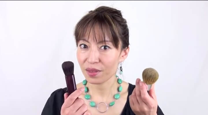 A woman with dark hair and bangs, and green necklace holding make-up brushes, one in each hand