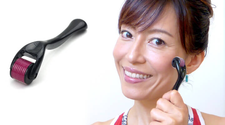 A woman with dark hair and bangs smiling while holding a derma roller on her cheek.