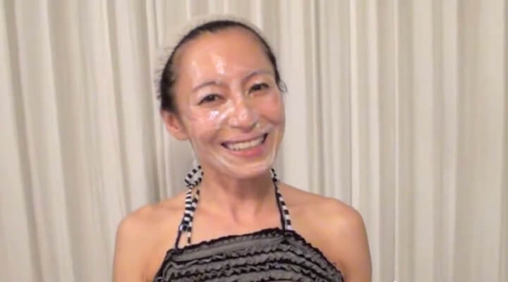 A woman with a shower cap and face covered in clear face mask smiling.
