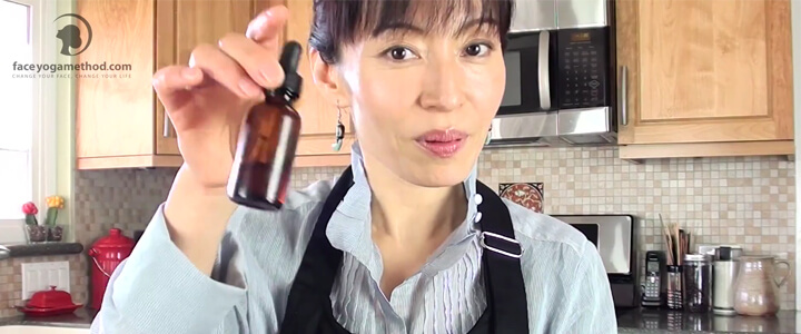 A woman with dark hair in the kitchen holding a little brown bottle in the air and looking straight at the camera