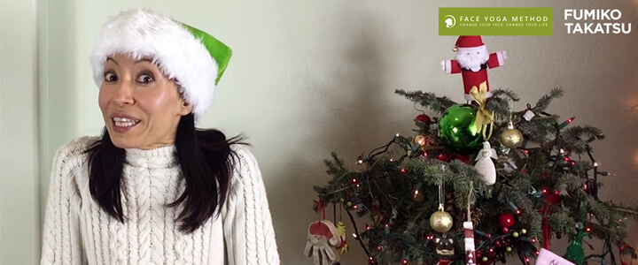 Woman with a green Santa Claus cap smiling next to a Christmas tree. Fumiko Takatsu wishing a happy New Year!