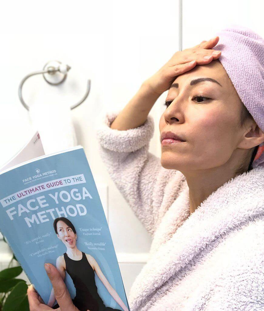 Fumiko in the bathroom reading the Ultimate Guide to the Face Yoga Method