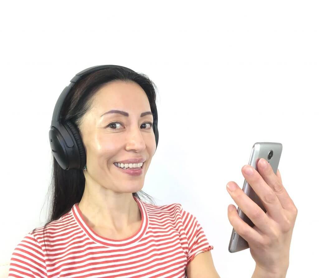 Woman with black hair with headphones on the head and a cellphone in the hand looking at the camera. Fumiko Takatsu on using earbuds and their benefits for symmetrical face.