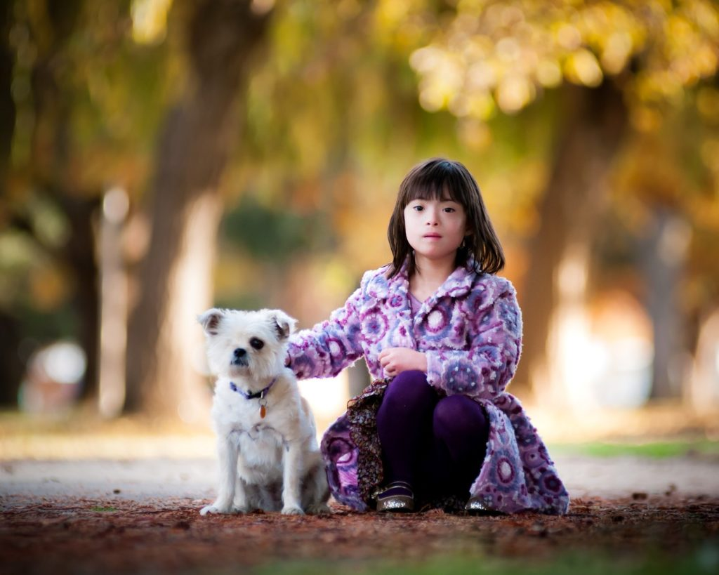 A girl in a purple coat sitting next to a white dog. Fall background.