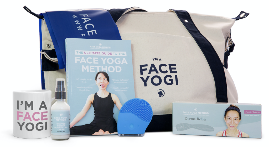 """A white duffle bag with """"I am a Face Yogi"""" print, surrounded by skincare products and devices - a facial cream bottle, a blue electric facial brush, a box with a facial roller with needles, a book, a white mug and a blue resistance band."""