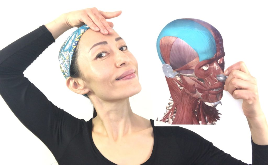 A woman with a blue cap touching her forehead and smiling, while holding a photo showing the musculature of human face.