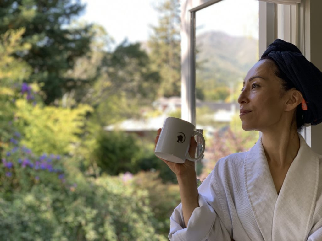 A woman with a turban sitting on the window and looking in the distance while holding a white coffee mug.