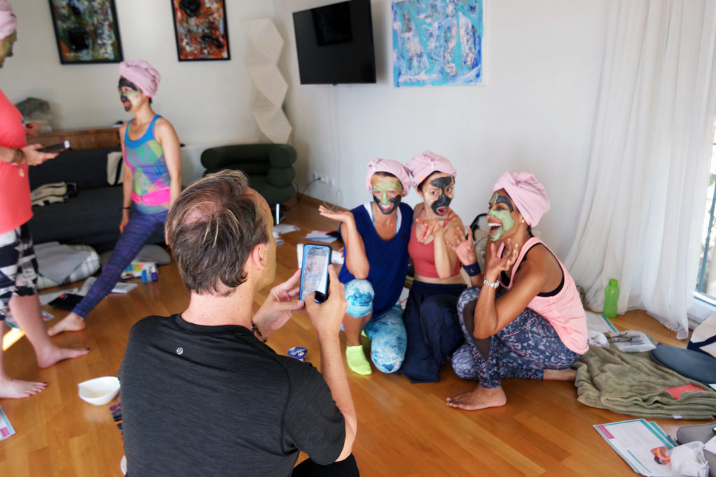 A group of people in exercising clothes with towel turbans and facial masks laughing and posing for a photo.