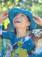 Fumiko Takatsu in a blue and green top showing excitement while smiling and holding her hands in her blue hat.