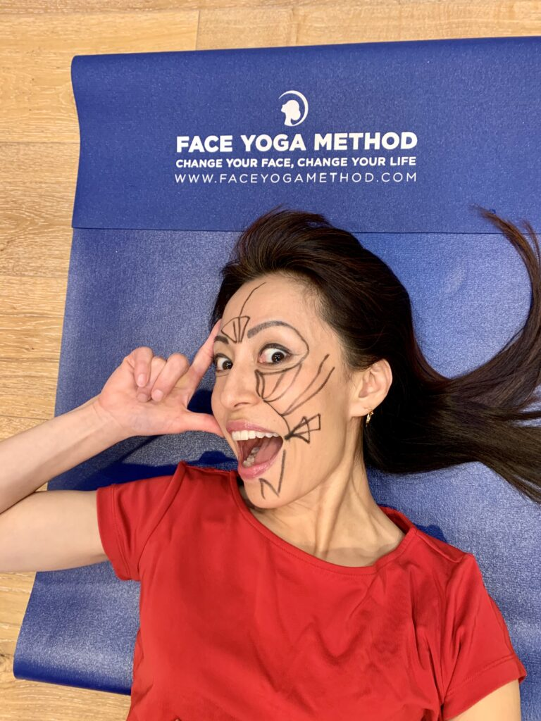 Fumiko Takatsu with drawings on her face, laying on a blue yoga mat and smiling.