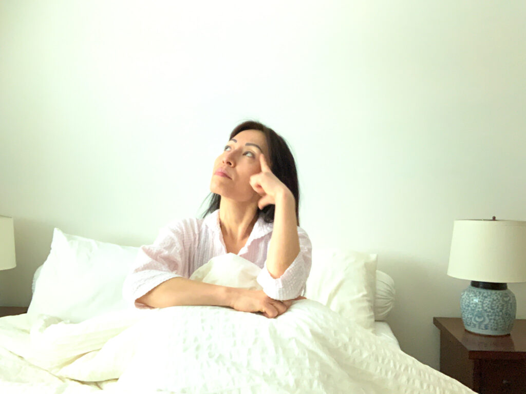 A woman in a bed sitting covered with sheets while looking like she is thinking about something.