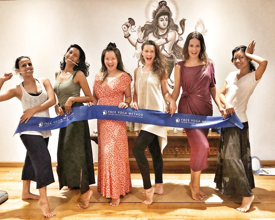 A group of women holding a Face Yoga Method posture band and striking different poses.